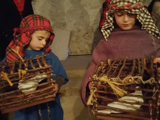 Shepherds, played by Calvin and Carter Steffes, hold cages of birds for the Live Christmas Nativity.