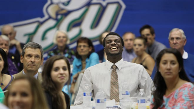 Marc-Eddy Norelia, center, laughs at his dance moves on the big screen during an end-of-the-season video presentation at the FGCU men's basketball banquet Tuesday in Fort Myers.