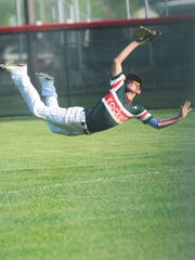 Oak Harbor's Ethan Schwaderer tries to make a catch against Port Clinton on Wednesday.
