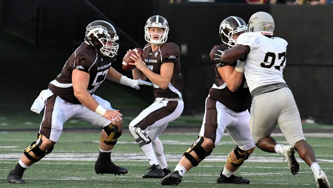 Western Michigan QB Jon Wassink (16) drops back to pass during game action Saturday night.