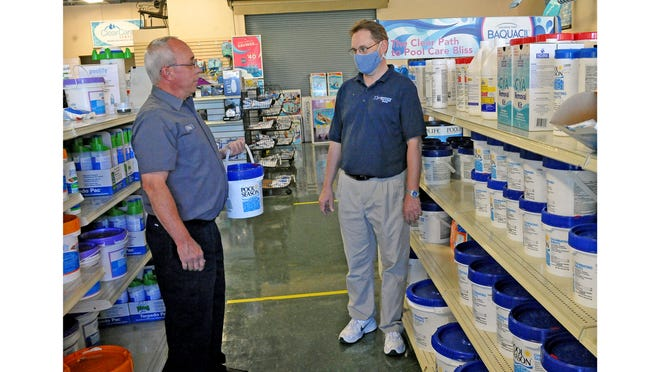 Gary Cassidy, a Litehouse Pool customer, speaks with manager Joe Bazan about water quality in his pool. Litehouse has seen its sales spike in every category as more people buy pools or use their home pools during the coronavirus pandemic.
