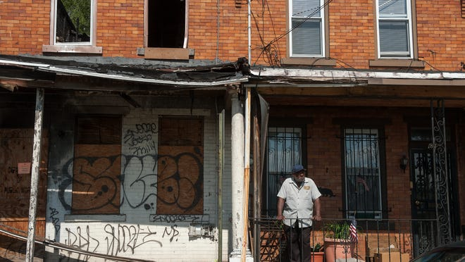 James Williams  looks out from his front porch home in Camden.Williams has suffered from three fires at abandoned homes next to him that the city has never addressed. 05.06.14