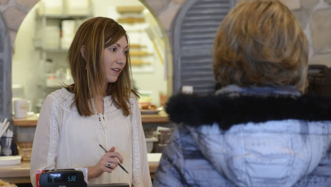 Kelly La Torre, owner of Alpha Delights European Bakery and Cafe, De Pere, assists customers.