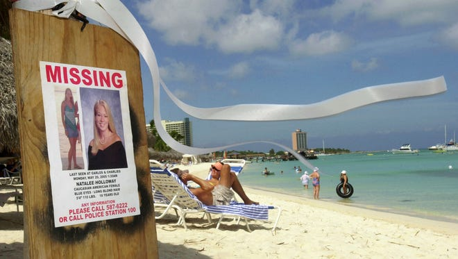 FILE - This June 10, 2005 file photo shows a missing poster for Natalee Holloway, a high school graduate of Mountain Brook, Alabama who disappeared while on a graduation trip to Aruba on May 30, 2005, on Palm Beach where tourists sunbathe in Aruba. Aruba prosecutors said Wednesday, May 20, 2015 a tip about the potential location of Holloway's body turned out to be false after spending weeks investigating the claim in the unsolved, decade-long disappearance of the U.S. teen. (AP Photo/Leslie Mazoch, File)
