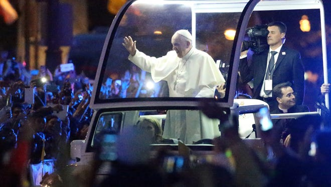 Pope Francis is illuminated from the Pope Mobile as he greets the many thousands of people attending the Festival of Families Saturday, Sept 26 in Philadelphia.