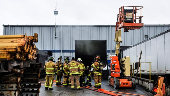 Fire fighters prepare to enter a section of the Royal Group building on Innovation Drive after responding to a call about a structure fire on Monday morning.