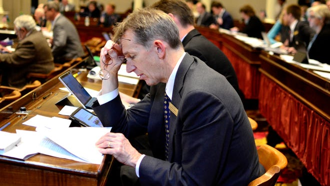 Rep. Charles Kimbell, D-Woodstock, examines documents during a discussion of a paid family leave insurance law at the Vermont House of Representatives on Tuesday, May 2, 2017.