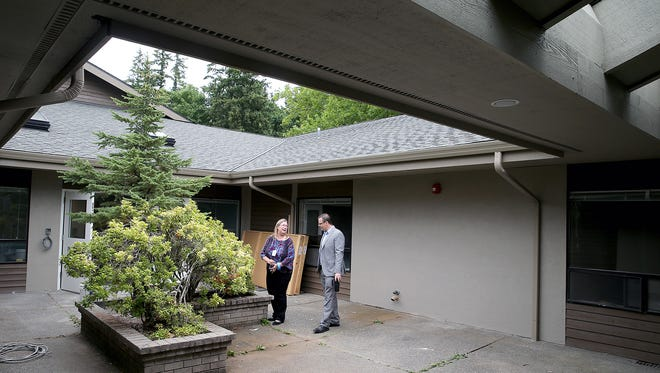 Rochelle Doan, center, and, Neil Olson Director, both of Kitsap Mental Health Services, stand in the courtyard of the long-awaited crisis triage center in East Bremerton, which opens on Aug. 1. The courtyard will be a reflective location for patients and will also have exercise equipment.