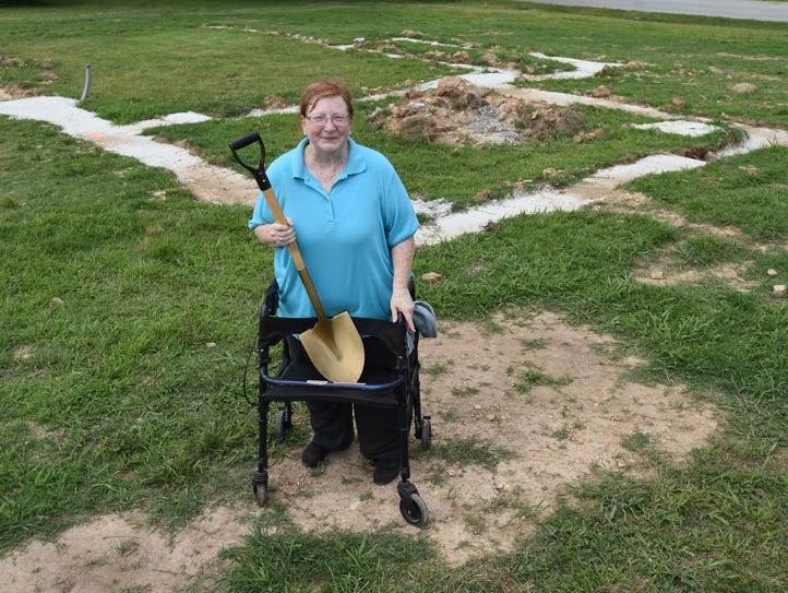 Nancy Neaves stands in the backyard of her future house