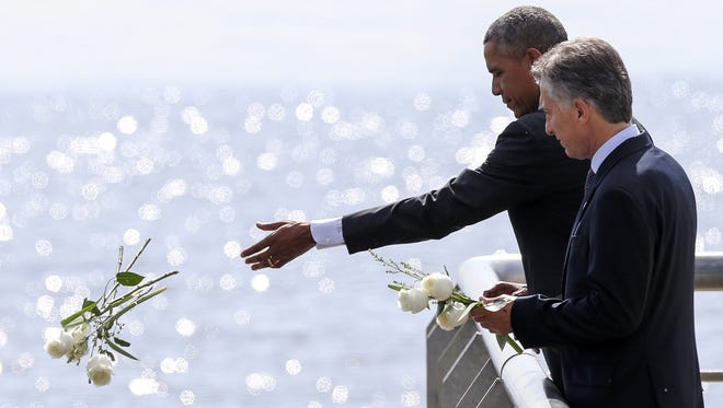 U.S. President Barack Obama, left, and his counterpart from Argentina Mauricio Macri, right, make a floral tribute to the victims of the military dictatorship at Parque de la Memoria in Buenos Aires, Argentina, March 24,  2016, during the tour of the wall, next to the Rio de la Plata.