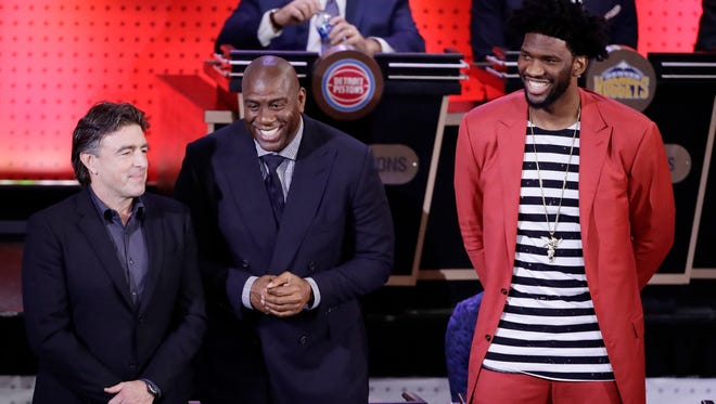 Boston Celtics co-owner Wyc Grousbeck, left, Magic Johnson, president of basketball operations for the Los Angeles Lakers, center, and Philadelphia 76ers' Joel Embiid, right, react after the learning they will get one of the first three picks as the NBA Draft lottery is announced.