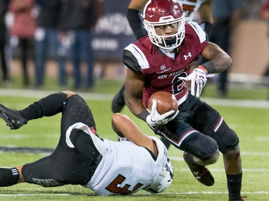 NMSU's wide receiver O.J. Clark shakes the tackle of Arkansas State's B.J. Edmonds for a nice gain Saturday night at  Aggie Memorial Stadium. 10/28/17