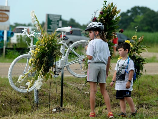 Rylie Lomas, 8, and her brother Slaydon, 6, reflect near the ghost bike memorial of their father Lon Lomas near the intersection of Mermentau Road and La. Highway 92 in Youngsville, LA, Sunday, July 13, 2014. Lon Lomas, an avid cyclist, was found dead near the intersection after a hit-and-run on Monday.  Photo by Paul Kieu, The Advertiser