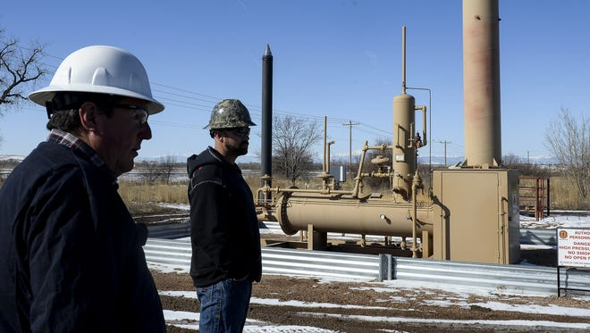 District Manager Steve Harris and Production Manager Tim Musgrave stand by one of Great Western's oil well sites March 6, 2015, in Windsor.