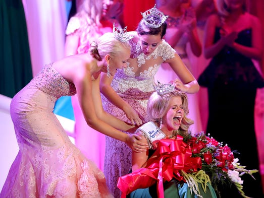 Audra Casterline, Miss Hoosier Heartland, reacts to being crowned Miss Indiana as Miss Indiana 2013 Terrin Thomas (back) and Miss Indiana Outstanding 2013 Teen Kylie Wheeler attempt to place the crown on her head during the Miss Indiana pageant on June 21, 2014, at Zionsville High School.
