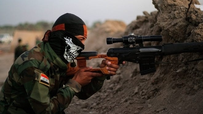 An Iraqi Shiite militiaman aims his weapon after clashes with militants from the Islamic State group, in Jurf al-Sakhar, 43 miles (70 kilometers) south of Baghdad, Iraq, on Sunday, Sept. 28, 2014.