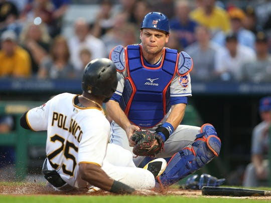 Pittsburgh Pirates right fielder Gregory Polanco (25) is tagged out at home plate while attempting to score against New York Mets catcher Devin Mesoraco (29) during the fourth inning at PNC Park.