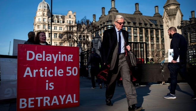"""Pro-Brexit protesters display a placard to passers-by outside the Houses of Parliament in London on February 21, 2019. Britain's finance minister Philip Hammond said Thursday there had been """"some movement"""" by the European Union that could lead to a breakthrough in Brexit talks in """"the next few days."""""""