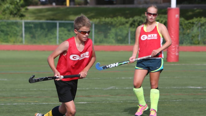 From left, Rye's Phile Govaert and his sister Fusine, take part in field hockey practice at Rye High School Aug. 20, 2015.