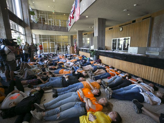 "High school students participate in a ""die-in"" in the"