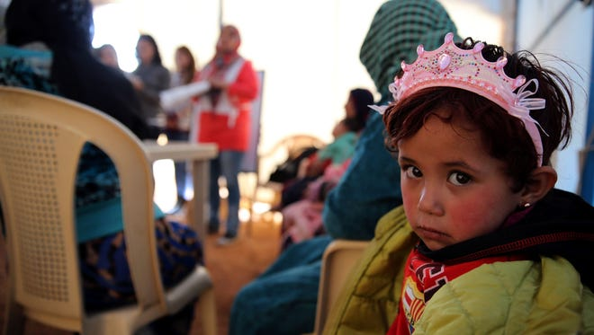 A child sits under a tent Sunday with Syrian refugees in Lebanon. Syria is in the midst of a civil war and is partly occupied by the Islamic State, also known as ISIS.
