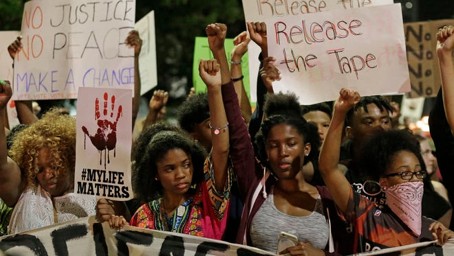 Protesters raises their fists as they march in the streets of Charlotte, N.C.on Sept. 23 over the fatal police shooting of Keith Lamont Scott.