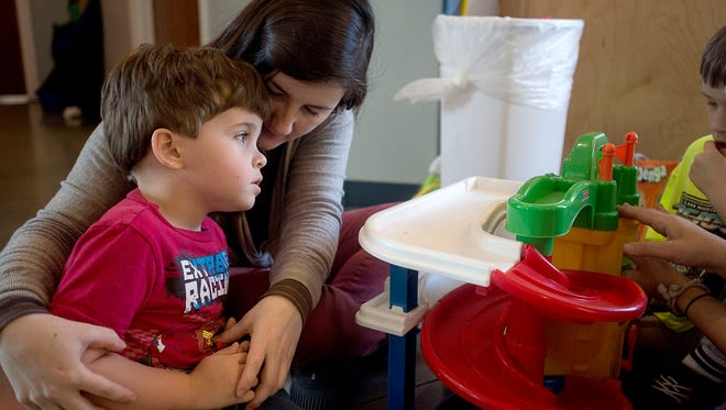 Behavior technician Megan Burton holds a child during playtime April 23, 2016 at the St. Gerard House in Hendersonville.