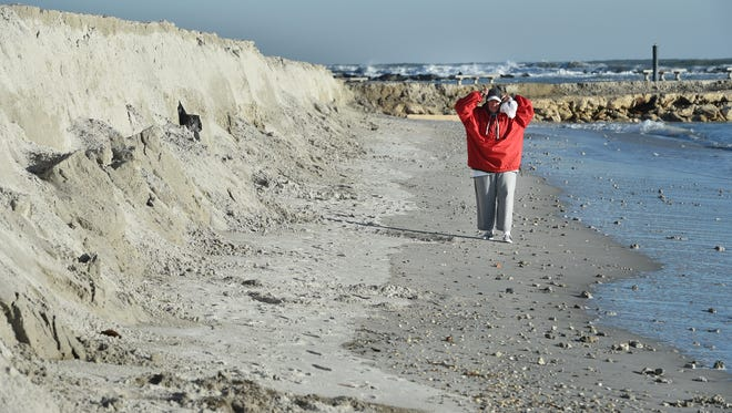 """Michelle Dekmar, of Fort Pierce, a former resident of New Jersey, adjusts her jacket hood while wandering the beach looking for shells by the Fort Pierce Jetty Thursday, Jan. 4, 2018, as temperatures from yesterday's cold front dipped into the low 30s. """"There was frost on my window this morning so it's cold, that's why there is nobody on the beach, but I like it,"""" Dekmar said."""