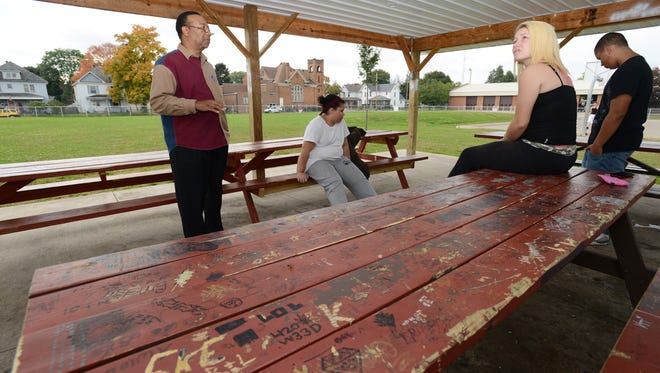 Coshocton City Council President Cliff Biggers talks with Nela Duerson, left, Nakeisha Ianniello and Brave Duerson about some of the vandalism done to the pavilion at Himebaugh Park in Coshocton. Council is considering surveillance equipment and taking other steps prevent the damage and to catch vandals in the act.