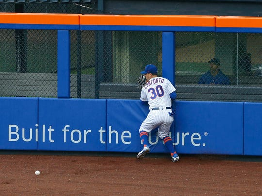 New York Mets left fielder Michael Conforto (30) run into the fence chasing a ball hit by Toronto Blue Jays left fielder Curtis Granderson (18) in the fifth inning at Citi Field.