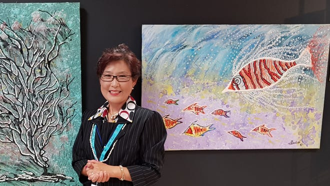 A Women's Art exhibit was held in honor of Women's History Month at the Infiniti Art Gallery, Nissan show room, Upper Tumon. The Soroptimist International of Guam, Guam Council of Women's Clubs, Guam Council on the Arts & Humanities Agency, Department of Chamorro Affairs and Isla Center for the Arts held this exhibit. Pictured is local artist Yeon Sook Park in front of the artwork Marine's Life Coral-16 and Aqua Marine Life-6.