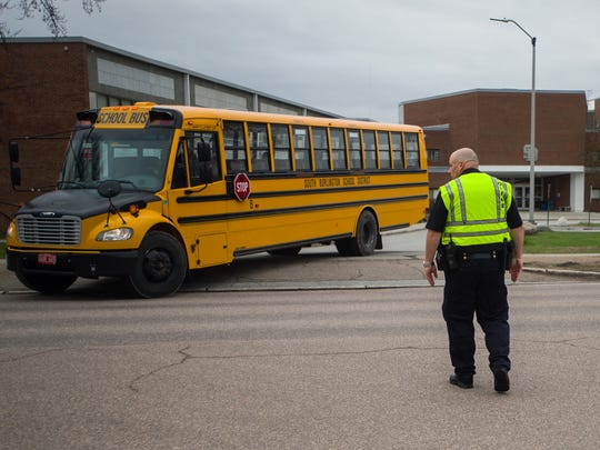 Police stop traffic on Dorset Street to allow buses evacuating South Burlington High School students to pass on Thursday, April 20, 2017, after the school went into lockdown.