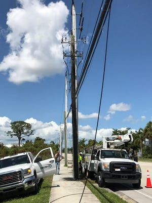 Comcast workers repair a broken cable Tuesday along Palm Beach Road in Stuart.