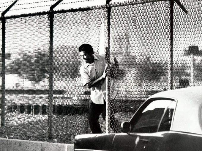 07 AUG 1979 - A man makes his way through the fence