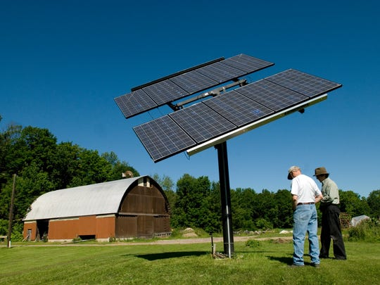 Plenty of questions: Visitors discuss the cost and benefits of a solar array in Colchester.