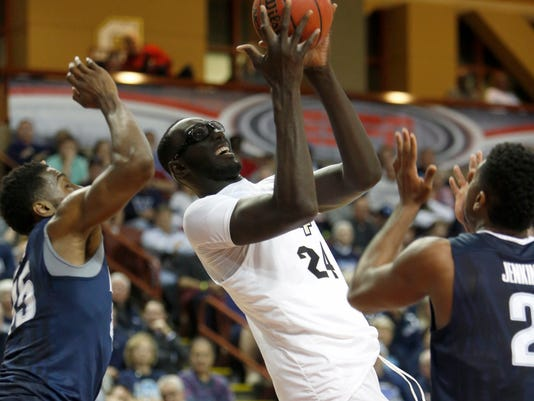 FILE - In this Sunday, Nov. 20, 2016, file photo, Central Florida's Tacko Fall, center, grabs a rebound over Villanova's Darryl Reynolds, left, and Kris Jenkins, right, during the first half of an NCAA college basketball game at the Charleston Classic at TD Arena, in Charleston, S.C. Central Florida has a new coaching staff, the program has new energy and Fall is getting more comfortable on the basketball court. (AP Photo/Mic Smith, File)