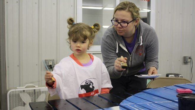 Kim Walls and her daughter, Nora, 3, work on one of the 96 panels painted during a community art making JAM Session in downtown Jeffersonville on Saturday.