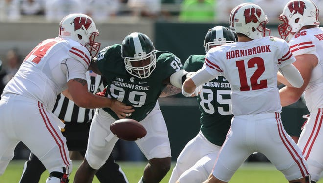 Michigan State Spartans' Raequan Williams forces a fumble by the Wisconsin Badgers' Alex Hornibrook on Sept. 24, 2016 at Spartan Stadium in East Lansing.