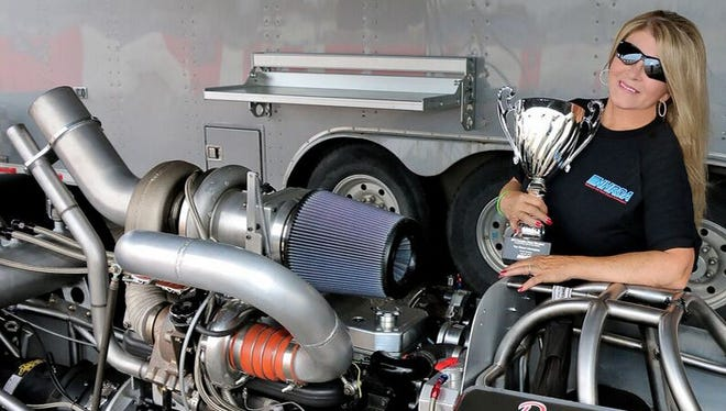 Great Falls' Dawna Kraus poses with her diesel drag racer and the trophy she won as Top Diesel National Champion last October in Texas.