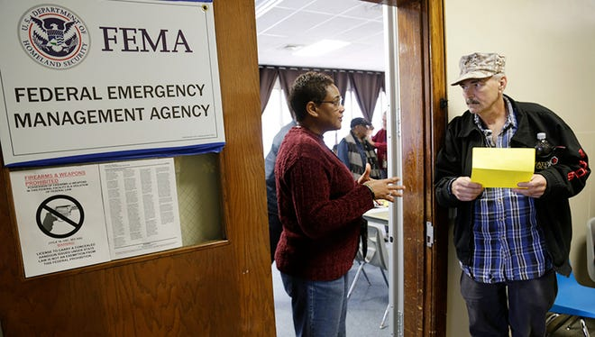 Eunice Bell, left, applicant services for The Federal Emergency Management Agency helps Harold Johnson of Hazel Park navigate getting assistance in the FEMA temporary disaster recovery center office inside the Gerry Kulick Community Center in Ferndale on Tuesday.
