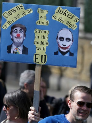 A demonstrator holds a placard depicting President Trump and Russia's President Vladimir Putin during an anti Brexit, pro-European Union (EU) march in London on March 25, 2017.
