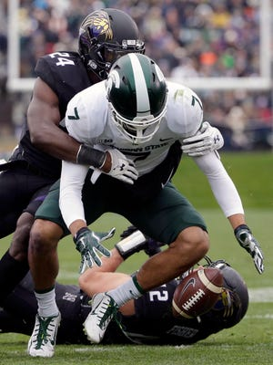 Michigan State wide receiver Cody White fumbles the ball while tackled by Northwestern cornerback Montre Hartage during the first half.