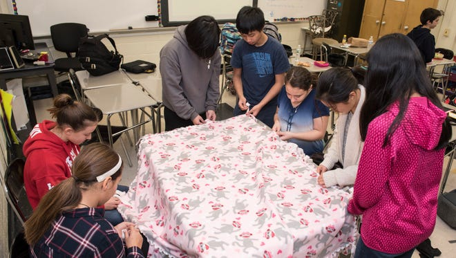 River Dell Middle School students from Miriam Gargiulo's 7th grade homeroom demonstrate how they make fleece blankets to donate to local charities on Tuesday December 19, 2017.