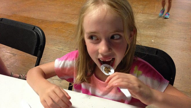 Anna Rose Burden tries dry roasted crickets during summer camp at the Belton Depot.