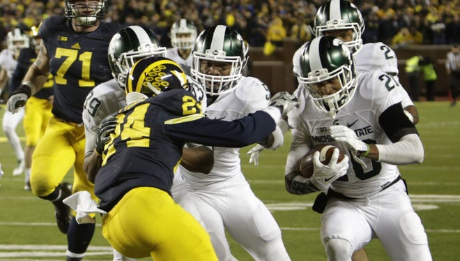 Michigan State's Jalen Watts-Jackson runs the ball down the side lines for the winning touchdown after he picked up a muff punt in the last 10 seconds of MSU's 27-23 win Saturday in Ann Arbor.