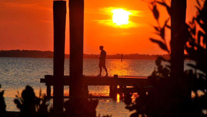 A man watches the sunset from the dock in south Cocoa Beach over the Banana River.