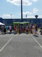 A large crowd waiting outside the Fuego Food Truck at a summer 2016 food festival.
