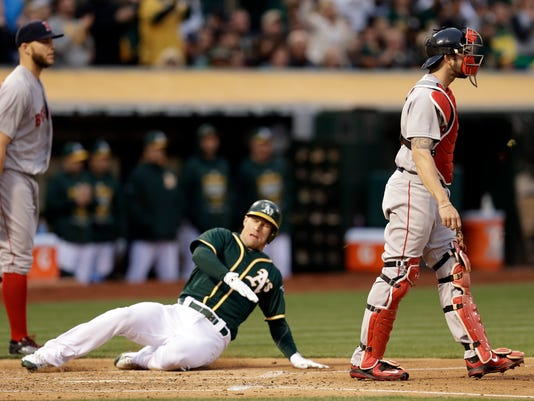 Oakland Athletics' Brett Lawrie, center, slides to score between Boston Red Sox pitcher Justin Masterson, left, and catcher Blake Swihart during the second inning of a baseball game Tuesday, May 12, 2015, in Oakland, Calif. (AP Photo/Ben Margot)