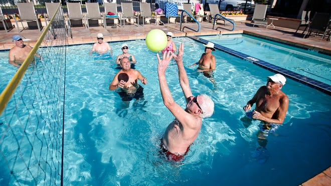 Wind chill is the farthest thing from these winter visitors' minds as they play a rousing game of water volleyball at Orangewood Shadows RV Resort in Mesa.
