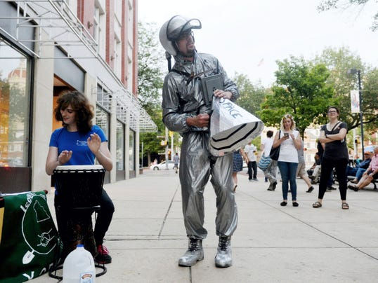 "With Tara Jean Mueller on percussion, self-described ""cosmosnaut"" Ian Carroll sings ""Benny and the Jets"" as a crowd gathers on West Market Street for the launching of ""Spaceship York"" on Friday. Operated by chief astronaut/enginner/dreamer William Chambers since April, Spaceship York has attracted more than 1,500 visitors who have contributed more than 300 dreams to the project."